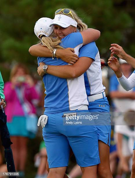 Anna Nordqvist of Sweden hugs Caroline Hedwall of Sweden and the European Solheim Cup team hug after Hedwall made a putt to win her match and retain...