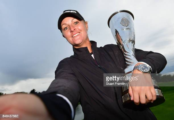 Anna Nordqvist of Sweden imitates a 'selfie' as she poses with the trophy after winning during the play off after the final round of The Evian...