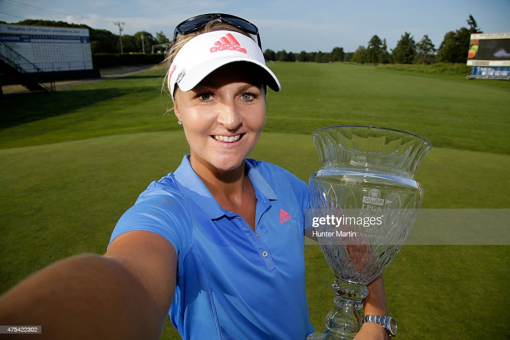 Anna Nordqvist of Sweden imitates taking a selfie with the championship trophy after winning the ShopRite LPGA Classic presented by Acer on the Bay...