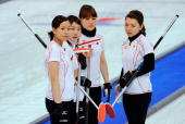 Anna Ohmiya Moe Meguro Mayo Yamaura and Mari Motohashi of Japan look on during a time out against Russia during the women's curling round robin game...