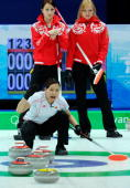Anna Ohmiya of Japan yells instructions to teammates as Ludmila Privivkova and Anna Sidorova of Russia look on during the women's curling round robin...