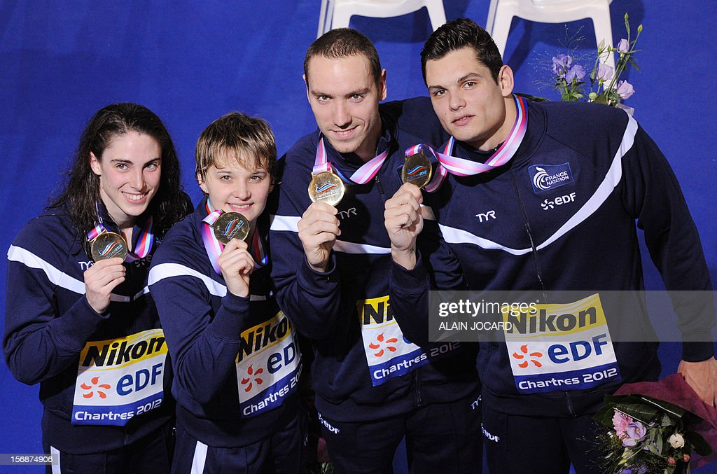 , Anna Santamans, Melanie Henique Jeremy Stravius and Florent Manaudou, pose with teir gold medal, after winning the mixed 4X50 medley final at the European Swimming Championships on November 23, 2012, in Chartres.