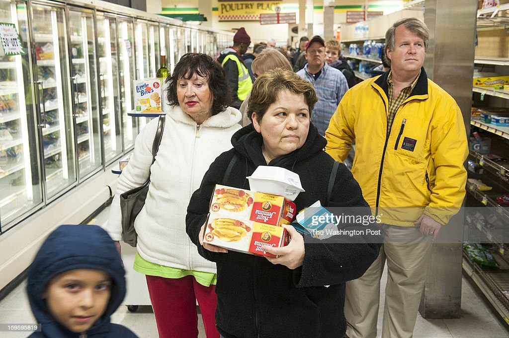 Anna Sosa with her son, Miguel, 8, stand in a line about 20 people deep as local grocery chain Magruder's is closing and offered 50 percent off Tuesday, January 15, 2013 in Gaithersburg, MD.