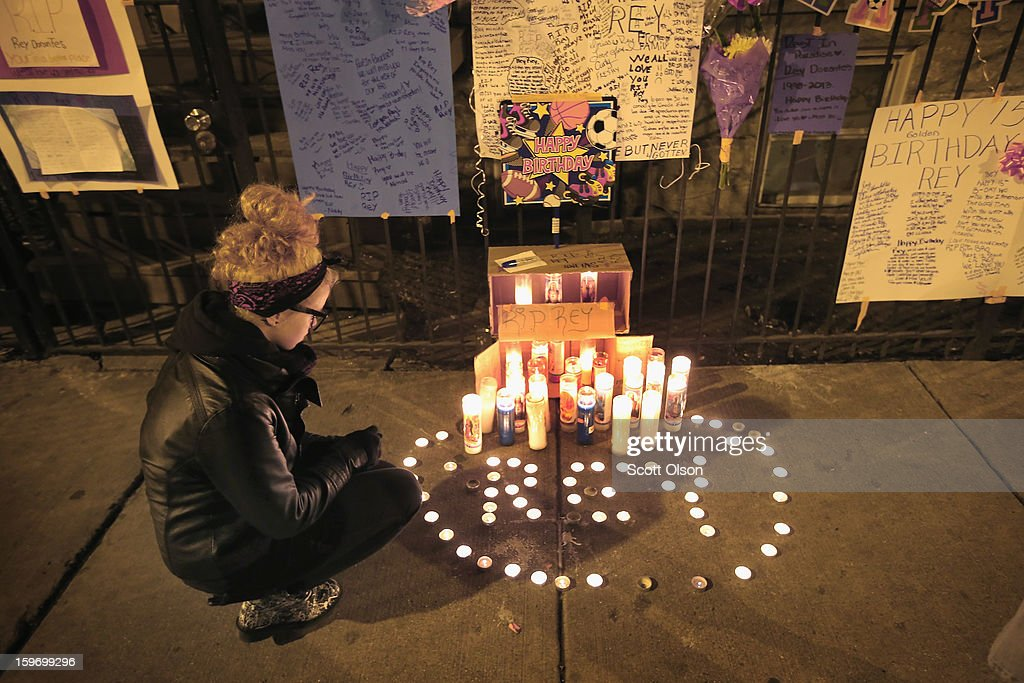 Anna Szydlo looks over a memorial in front of the home of Rey Dorantes on what would have been his 15th birthday on January 15, 2013 in Chicago, Illinois. Dorantes died after being shot 6 times while he was sitting on the front porch of his home on January 11. Dorantes' murder was the 21st homicide recorded in Chicago for 2013, a city which saw more than 500 homicides in 2012.