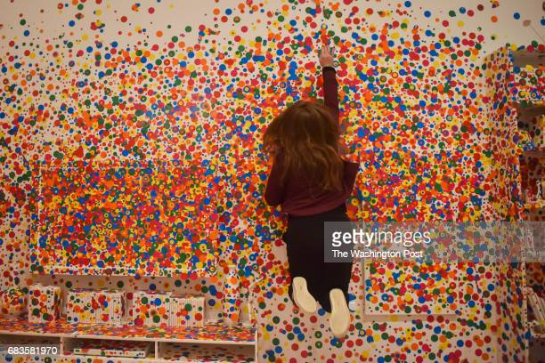 Anna Tulchinskaya leaps to apply the absolute last dot to the Obliteration Room on the final day of the Yayoi Kusama Infinity Mirrors exhibit at the...