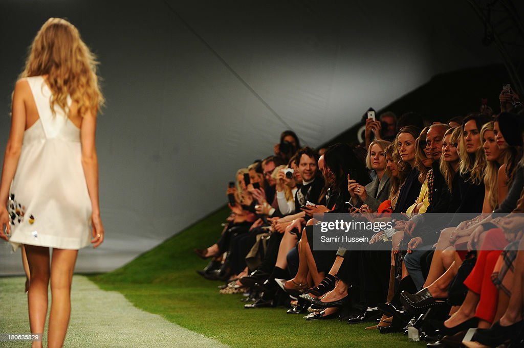 Anna Wintour, Philip Green, <a gi-track='captionPersonalityLinkClicked' href=/galleries/search?phrase=Kate+Moss&family=editorial&specificpeople=201830 ng-click='$event.stopPropagation()'>Kate Moss</a> and <a gi-track='captionPersonalityLinkClicked' href=/galleries/search?phrase=Ellie+Goulding&family=editorial&specificpeople=6389309 ng-click='$event.stopPropagation()'>Ellie Goulding</a> watch as <a gi-track='captionPersonalityLinkClicked' href=/galleries/search?phrase=Cara+Delevingne&family=editorial&specificpeople=5488432 ng-click='$event.stopPropagation()'>Cara Delevingne</a> walks the runway at the Unique show during London Fashion Week SS14 at TopShop Show Space on September 15, 2013 in London, England.