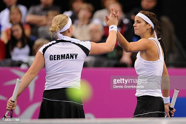 AnnaLena Groenefeld of Germany and teammate Julia Goerges high five during their double match against Barbora Zahlavova Strycova and Iveta Benesova...