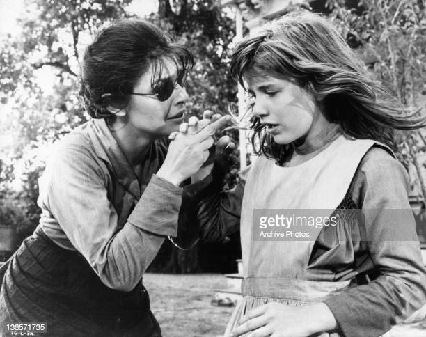 Anne Bancroft holding Patty Duke's hand to teach her a new word in a scene from the film 'The Miracle Worker' 1962