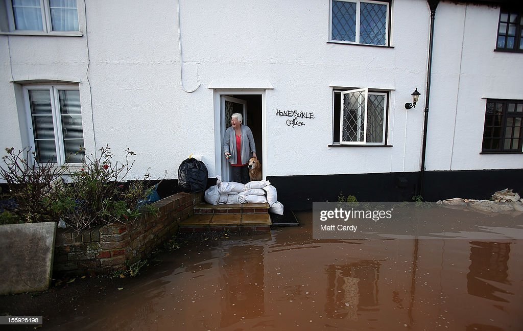 Anne Bartlett and her dog Henry look out from their flooded property in the centre of the village of Ruishton, near Taunton, is seen on November 25, 2012 in Somerset, England. Another band of heavy rain and wind continued to bring disruption to many parts of the country today particularly in the south west which was already suffering from flooding earlier in the week.