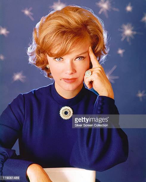Anne Francis US actress poses with a finger resting on aher temple in a studio portrait against a blue background with stars circa 1975