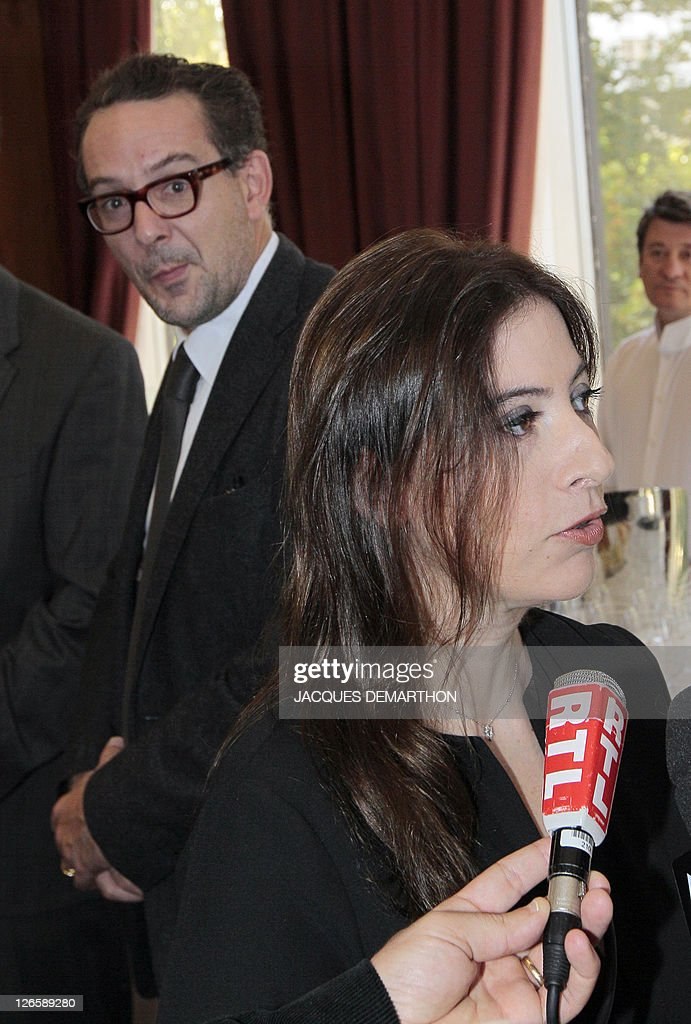 Anne Goscinny (R), the daughter of French scriptwriter Rene Goscinny who created the cartoon character 'Asterix the Gaul', answers journalists' questions, in front her husband Aymar du Chatenet (L) managing editor of the publishing house IMAV during a reception to mark the 350 millionth copy of the 34 Asterix books sold worldwide, at the French book group Hachette headquarters in Paris on September 26, 2011. AFP PHOTO JACQUES DEMARTHON