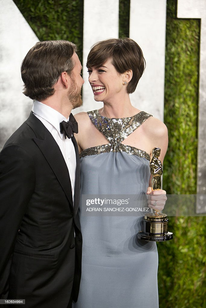 Anne Hathaway carrying her Oscar for best supporting actress and her husband arrive for the 2013 Vanity Fair Oscar Party on February 24, 2013 in Hollywood, California. AFP PHOTO / ADRIAN SANCHEZ-GONZALEZ