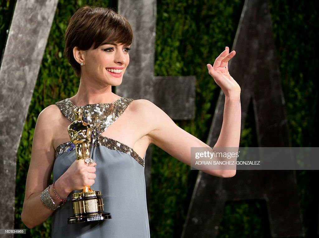 Anne Hathaway carrying her Oscar for best supporting actress arrives for the 2013 Vanity Fair Oscar Party on February 24, 2013 in Hollywood, California.