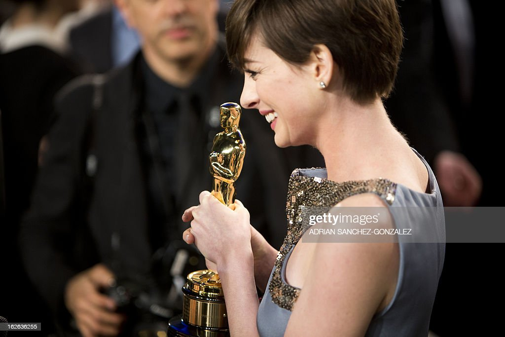 Anne Hathaway displays her Oscar for best supporting actress after arriving for the 2013 Vanity Fair Oscar Party on February 24, 2013 in Hollywood, California.
