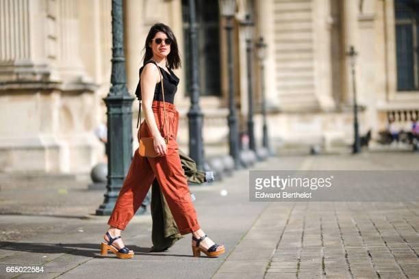 Anne Laure SasMayaux from the blog L'Atelier d'Al wears a Zara green trench Mango orange pants a Lancel bag Nice Thing shoes Izipitzi sunglasses at...