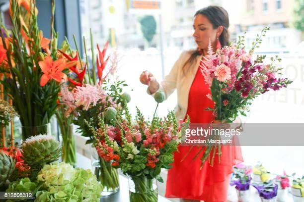 Anne Steiner business partner of 'Kians Garden Flower Shop' binds flowers during the 'Kians Garden Flower Shop' Opening Event at Kantstrasse on July...