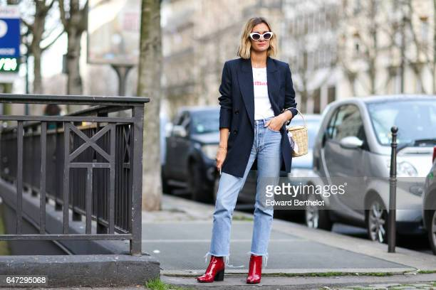 AnneLaure Mais fashion blogger from Adenorah wears a black jacket a white top blue denim jeans pants and red shoes outside the Alexis Mabille show...