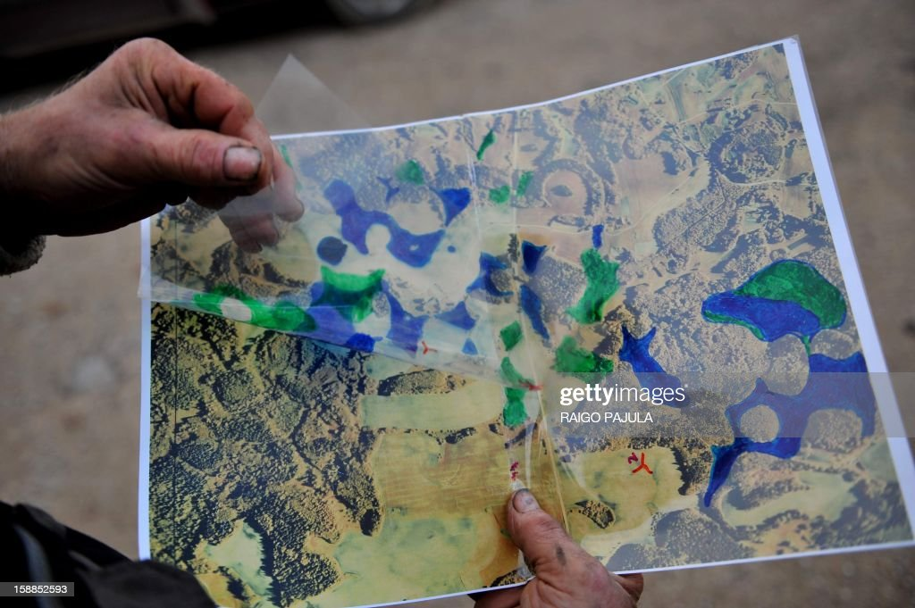 Anneli REIGAS Leigo music festival organizer, Estonian farmer Tonu Tamm, 71, who created 14 artificial lakes shows a map of his land before and after on December 15, 2012 in Leigo. Estonian Tonu Tamm has dedicated the past two decades of his life to his obsession of creating artificial lakes. AFP PHOTO / Raigo Pajula