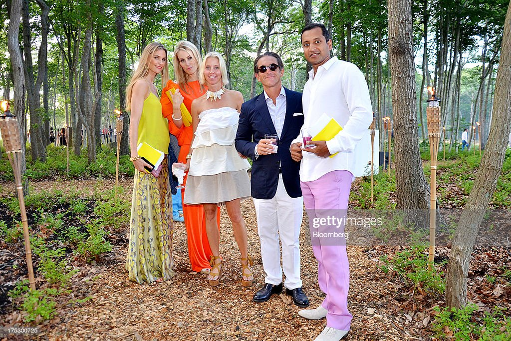 Annelise Peterson, director of client relations and special projects at Net-A-Porter Group Ltd., from left, Carola Jain, senior director at Interbrand Corp., Gigi Grimstad, partner of the Nashville fashion boutique Jamie Inc., Carl Grimstad, president and chief executive officer of Ipayment Inc., and Robert Jain, managing director and head of alternative investments at Credit Suisse AG, gather for a group portrait during the 20th annual Watermill Center benefit in Water Mill, New York, U.S., on Saturday, July 27, 2013. The event raised $1.85 million. Photographer: Amanda Gordon/Bloomberg via Getty Images