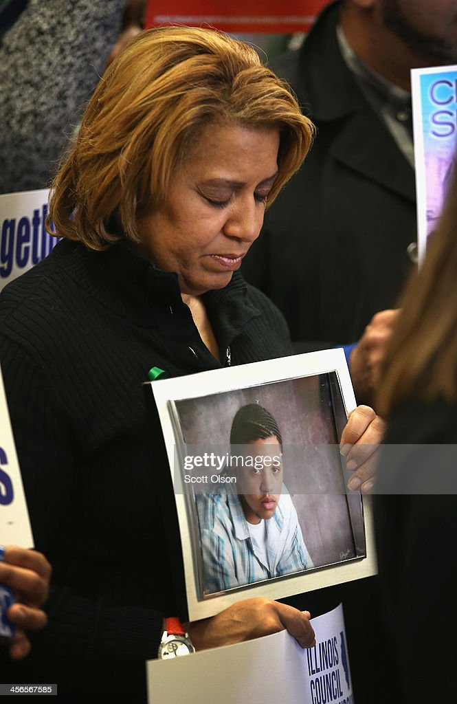 Annette Nance-Holt holds a picture of her son Blair during a gathering of gun violence victims and gun control advocates at Cornell Square Park on the anniversary of the Sandy Hook Elementary School shooting December 14, 2013 in Chicago, Illinois. Thirteen people, including a three-year-old boy, were wounded when gunmen opened fire on a crowd gathered at the basketball courts in Cornell Square Park in September. Twenty children and 6 adults were killed when a gunman opened fire at Sandy Hook School. Blair, 16, was killed riding a bus on his way to help out at his grandparents store in May 2007. His teenaged killer was sentenced to 100 years in prison. Nearly 1000 people have been murdered in Chicago in the past two year, most by gunfire.