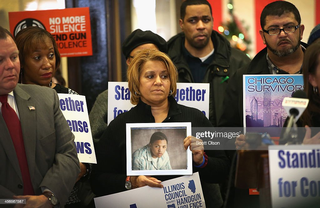 Annette Nance-Holt (C) holds a picture of her son Blair during a gathering of gun violence victims and gun control advocates at Cornell Square Park on the anniversary of the Sandy Hook Elementary School shooting December 14, 2013 in Chicago, Illinois. Thirteen people, including a three-year-old boy, were wounded when gunmen opened fire on a crowd gathered at the basketball courts in Cornell Square Park in September. Twenty children and 6 adults were killed when a gunman opened fire at Sandy Hook School. Blair, 16, was killed riding a bus on his way to help out at his grandparents store in May 2007. His teenaged killer was sentenced to 100 years in prison. Nearly 1000 people have been murdered in Chicago in the past two year, most by gunfire.
