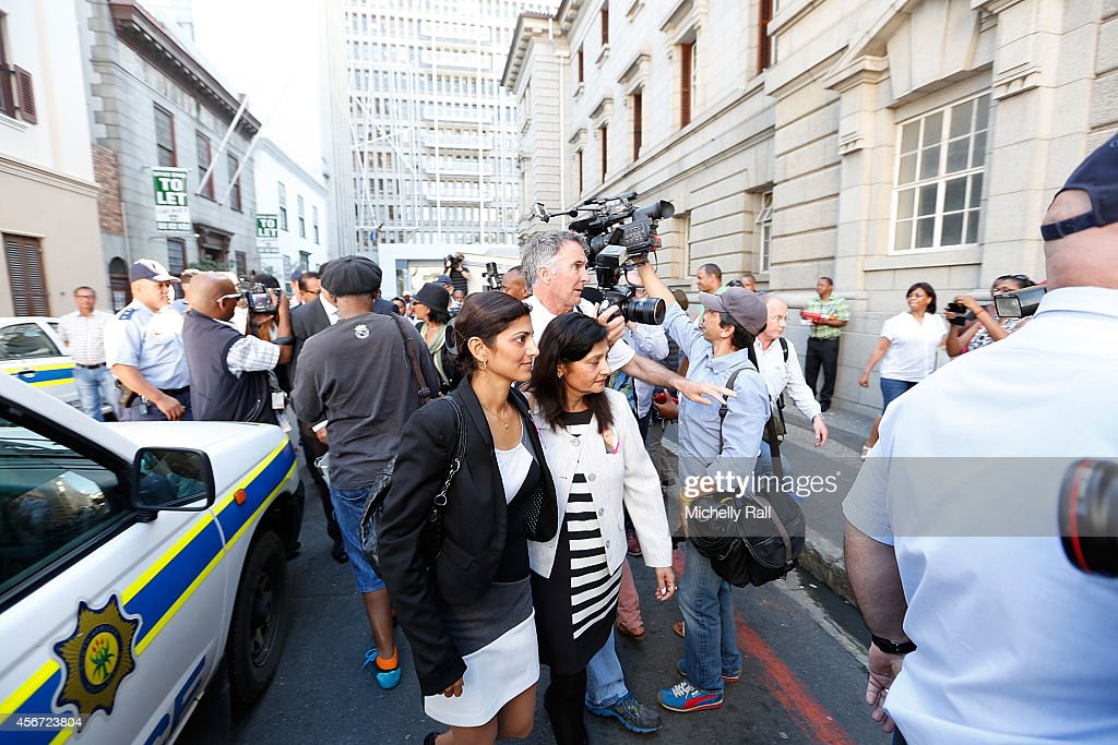 Anni Dewani's sister Ami Denborg (L) and mother Nilam Hindocha (R) arrive at the Western Cape High Court for the start of the trial of Shrien Dewani, on October 6, 2014 in Cape Town, South Africa. The British businessman, who fought an extradition battle for three years, is accused of arranging the murder of his new wife in 2010, just days after their marriage. A South African taxi driver and two accomplices are serving prison sentences for their connection with the murder of Mrs Dewani.
