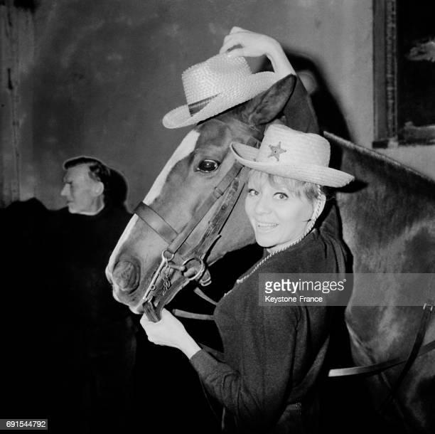Annie Cordy baptisant le chapeau texan nouveauté de l'été lancé par le comité de rayonnement de l'élégance française au manège de Neuilly France le...