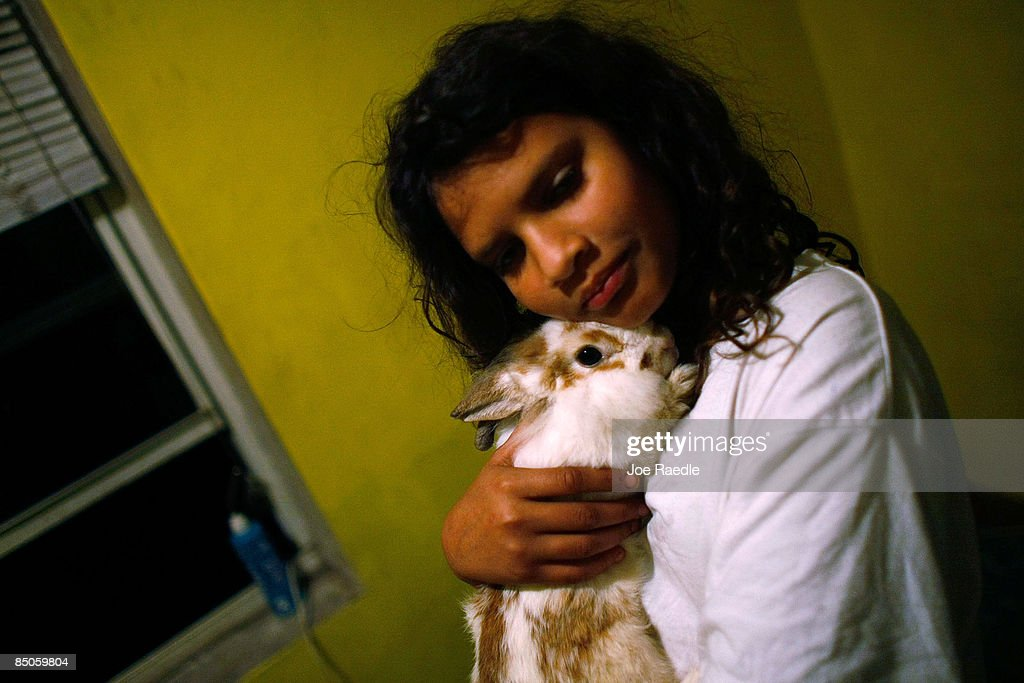 Annie Thomas holds her pet rabbit in the foreclosed home that she and her family reoccupied after busting the locks and moving in with the help of the activist group 'Take Back the Land' February 24, 2009 in Miami, Florida. The family was evicted from the home and had been living in a van in the parking lot of a local supermarket since Friday when they were evicted. Mary Trody, her husband and her two children were living in the house and could not pay their bills due to what she says was predatory lending by a mortgage company. Her husband lost his job, which forced the couple and their two teenage children along with other relatives to move back in to the house before they lost it to foreclosure and now the bank owns the house.