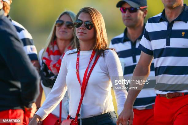 Annie Verret walks to the Trophy presentation holding hands with Jordan Spieth of the United States at the Presidents Cup on October 1 at Liberty...