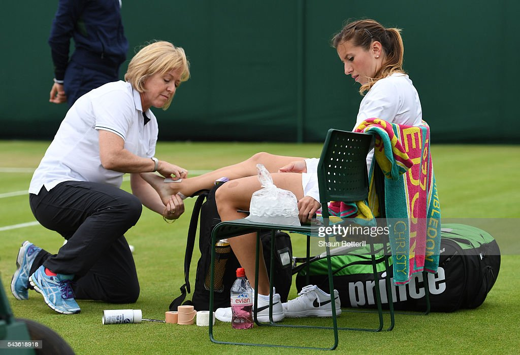 <a gi-track='captionPersonalityLinkClicked' href=/galleries/search?phrase=Annika+Beck&family=editorial&specificpeople=6249693 ng-click='$event.stopPropagation()'>Annika Beck</a> of Germany recieves treatment during the Ladies Singles second round match against Heather Watson of Great Britain on day three of the Wimbledon Lawn Tennis Championships at the All England Lawn Tennis and Croquet Club on June 29, 2016 in London, England.