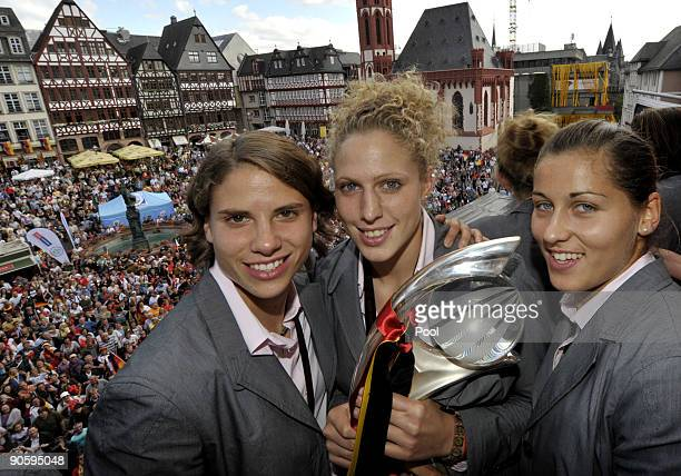 Annike Krahn Kim Kulig and Lisa Weiss celebrate during a reception for the German women's national team on the balcony of the city hall 'Roemer' on...