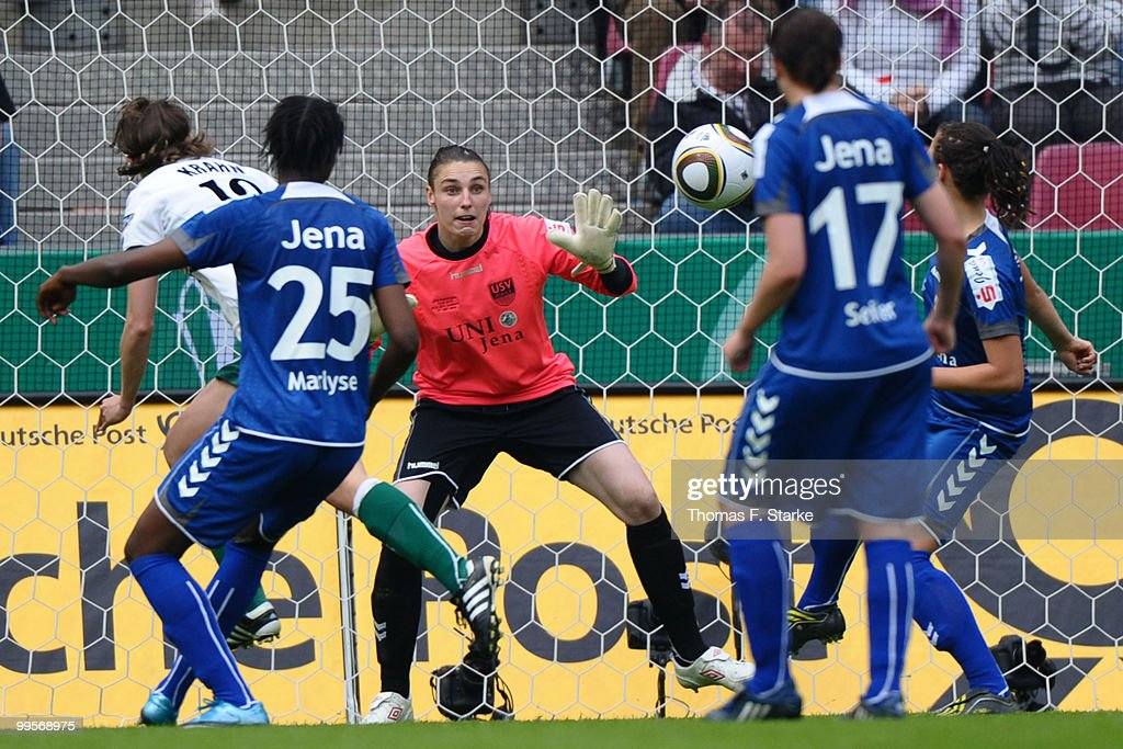 Annike Krahn of Duisburg scores against Marlyse Ngo Ndoumbouk and Jana Burmeister of Jena during the DFB Women's Cup final match between FCR 2001...