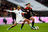 Annike Krahn of Germany is tackled by Lianne Sanderson of England during the Women's International Friendly match between England and Germany at...