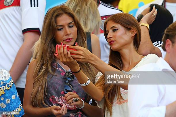 AnnKathrin Brommel girlfriend of Mario Gotze of Germany and Cathy Fischer girlfriend of Mats Hummels of Germany look on during the 2014 FIFA World...