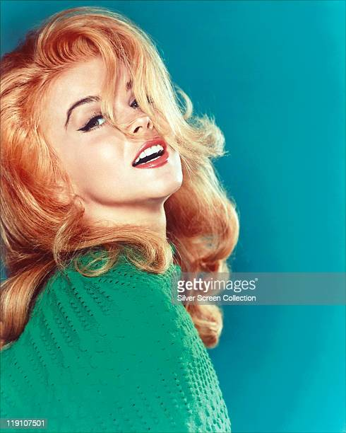 AnnMargret SwedishAmerican actress wearing turquoise blue woollen jumper in a studio portrait against a blue background circa 1965