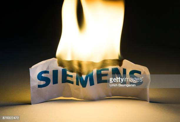Announced plant closures and job cuts turbulence at Siemens AG The photo shows a burning Siemens logo