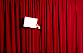 Announcement in front of red theatre curtains