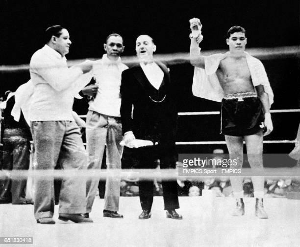 Announcer Harry Balogh second right raises the hand of the victorious Joe Louis right watched by Louis's trainer Jack 'Chappie' Blackburn second left