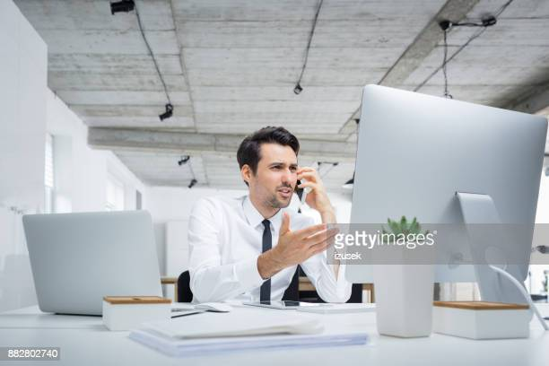 Annoyed businessman talking on phone in office