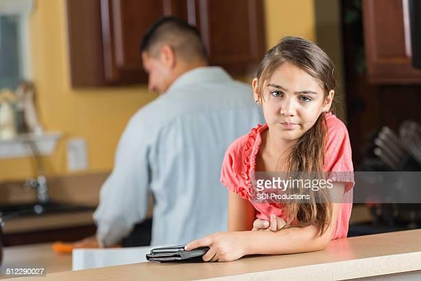 Annoyed little girl using digital tablet device at dinnertime