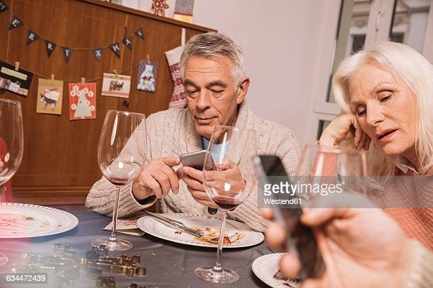 Annoyed senior woman with husband using smartphone after Christmas dinner