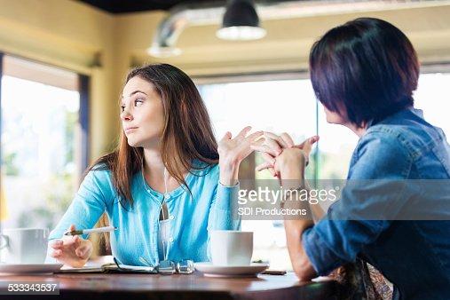 Molesto teen girl talking a la madre en la cafetería