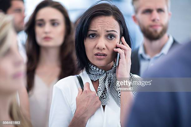 Annoyed woman on cell phone in busy city