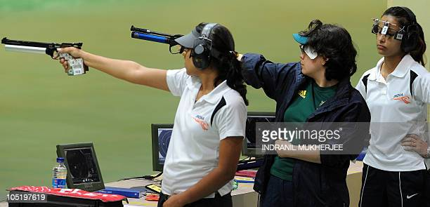 Annu Raj Singh of India and Dina Aspandiyarova of Australia fires a shot as Heena Sidhu concentrates before firing a shot in the women's pairs 10m...