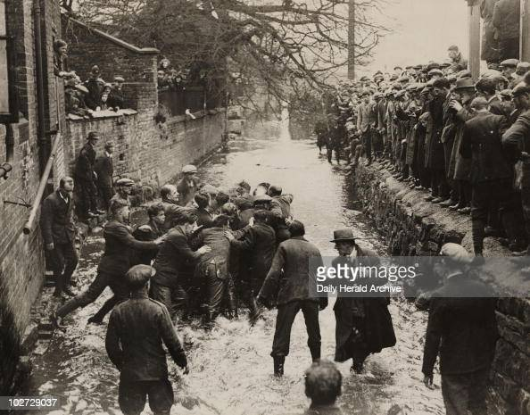 'Annual Shrovetide Football at Ashbourne' 1932 A photograph of players fighting for the ball in Henmore Brook during the Shrovetide football match in...
