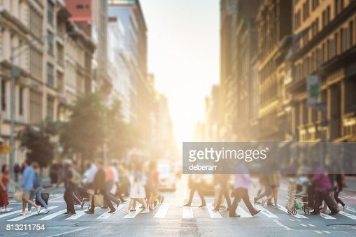 Anonymous group of people walking across a pedestrian crosswalk on a New York City street with a glowing sunset light shining in the background : Stock Photo