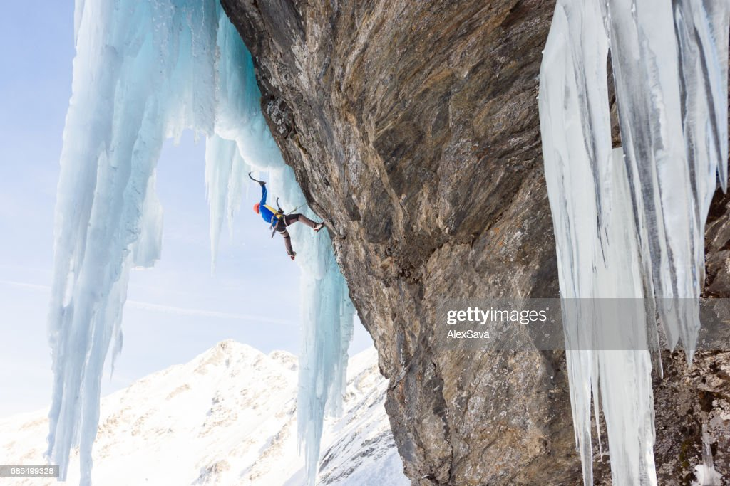 Anonymous man ice climbing on massive icicles : Stock Photo