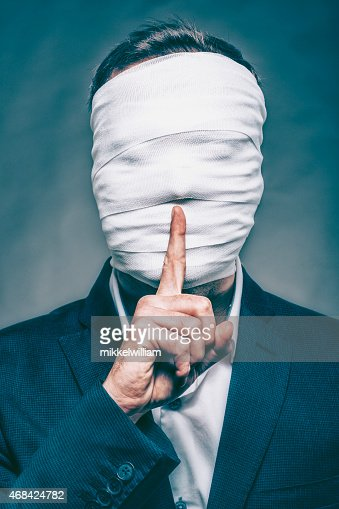 Anonymous man with face hidden makes sign to be silent