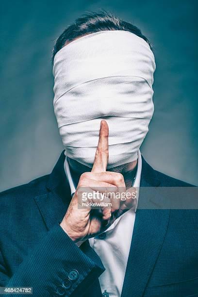 Anónimo hombre con cara oculta convierte señal de silencio