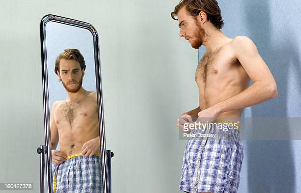 Anorexic man looking worried into mirror